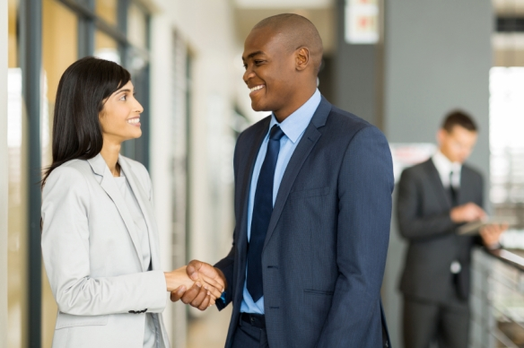 indian businesswoman handshaking with african businessman