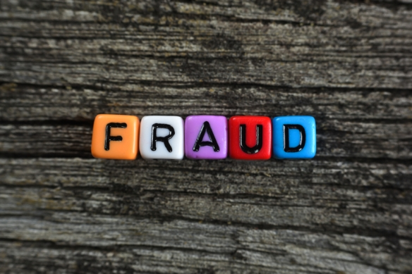 concept of fraud word on wooden background